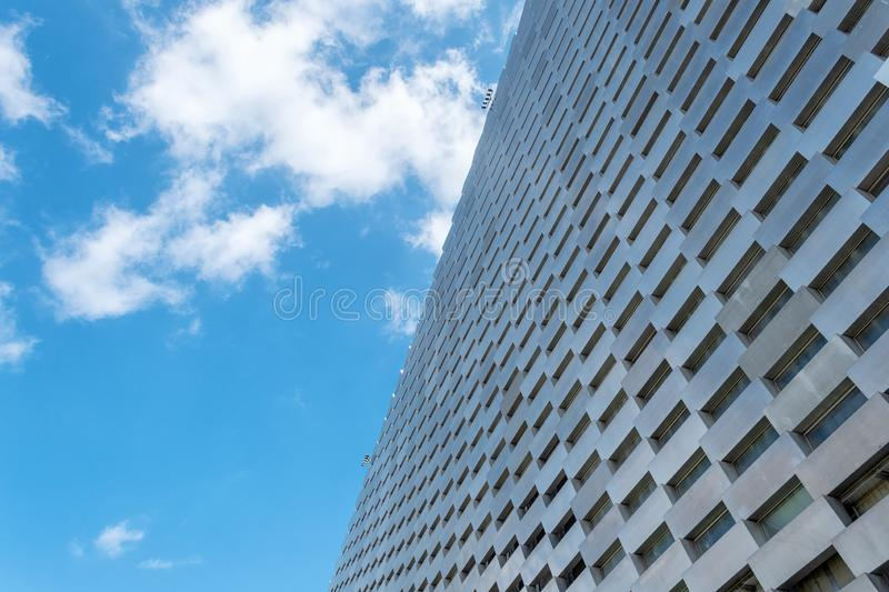 Facade of a modern metal building against a cloudy sky. Bottom view Architecture. Background stock photo