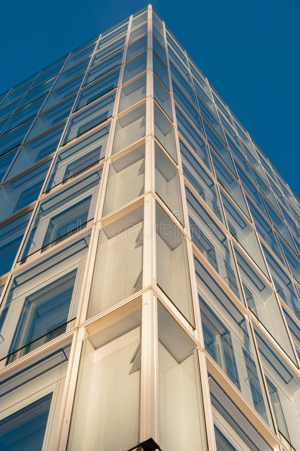 Facade of a modern office building with elements of glas and steel under a blue sky. stock images