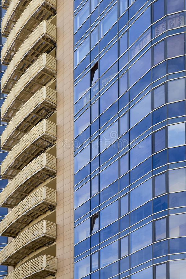 The facade of a modern office building made of glass and concrete. Vertically stock photos