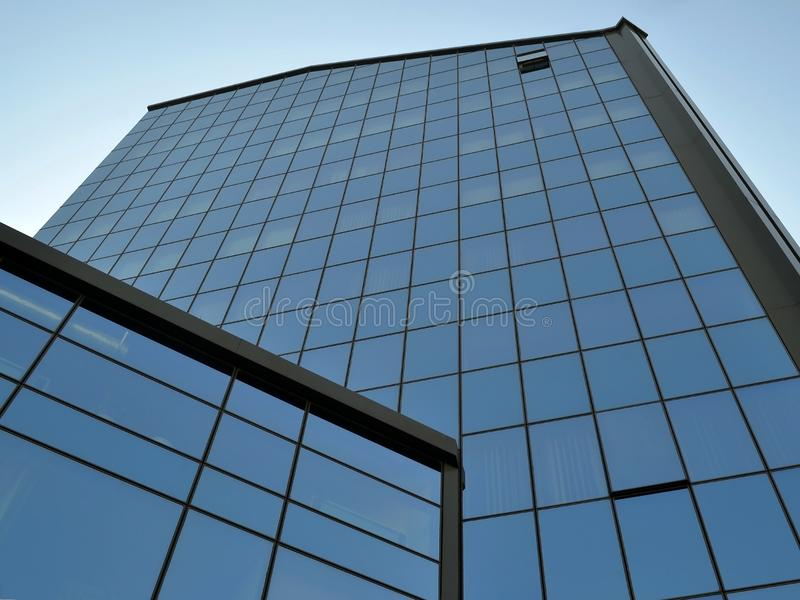 Facade of a modern office building made of glass and concrete with mirror windows against the blue summer sky on a summer day royalty free stock photo