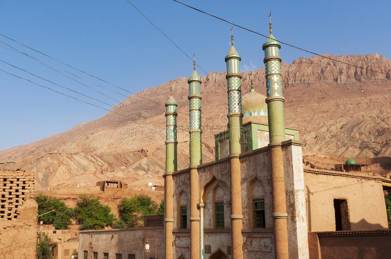 The facade of the mosque at the Uyghur village of Tuyog, with mountains on the background, Xinjiang region royalty free stock photos