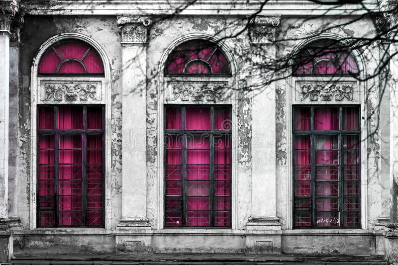 Facade of old abandoned building with three large arched windows of pink glass. Monochrome background stock photo