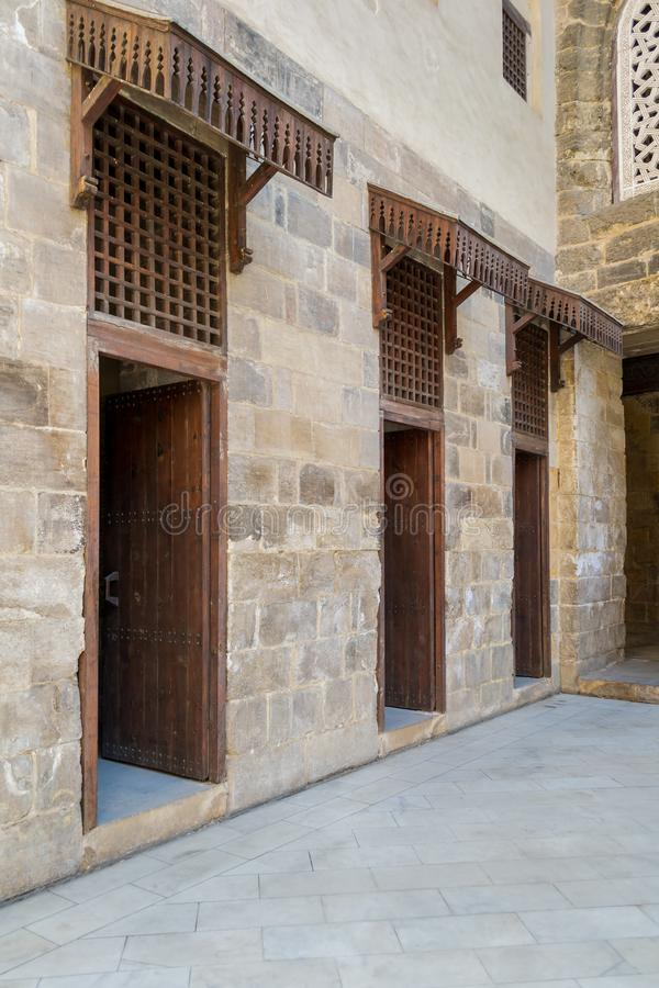 Facade of old abandoned stone bricks wall with three open weathered wooden doors. And windows covered with wooden grid, Old Cairo, Egypt royalty free stock photos