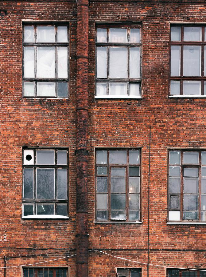 Facade of an old brick building in loft style. High Windows and textural materials. Architectural background stock photo