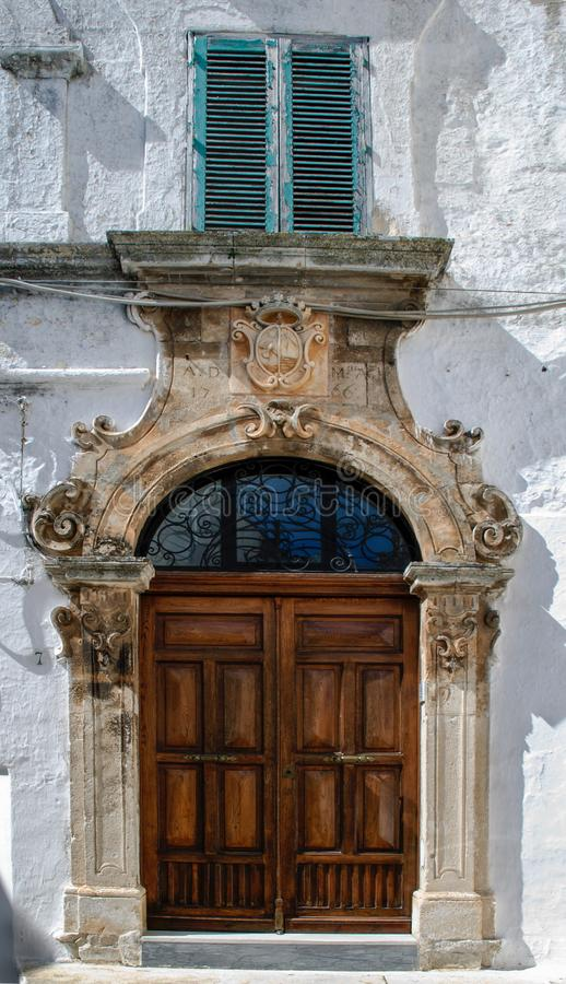 Facade of old building with magnificent door in the old town of Ostuni, La Citta Bianca royalty free stock images