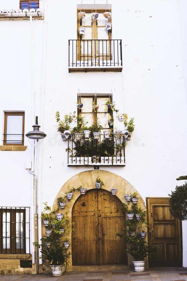 Facade of old European house with windows, balcony with flowers, wooden door in the shape of an arch.  royalty free stock image