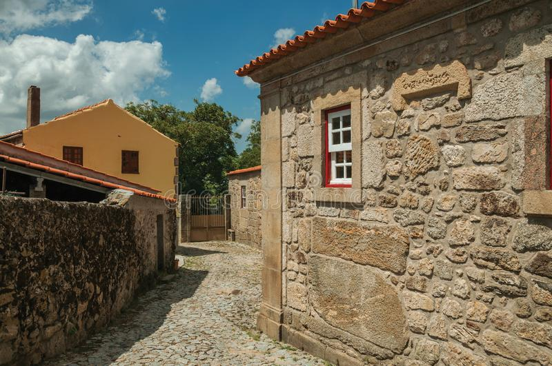 Old house with stone wall and small window in an alley stock photos