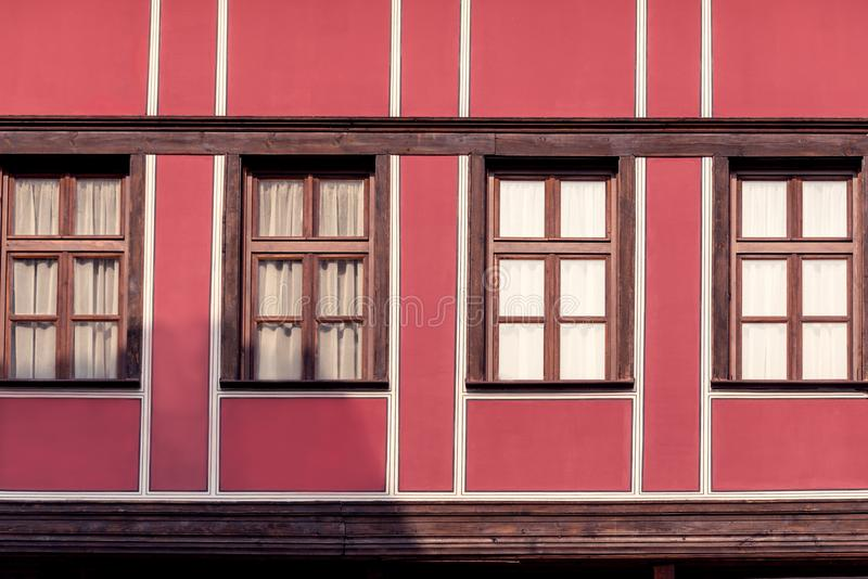 Facade of old, red, historical building with four windows. Facade of old, red, historical building with four windows stock images