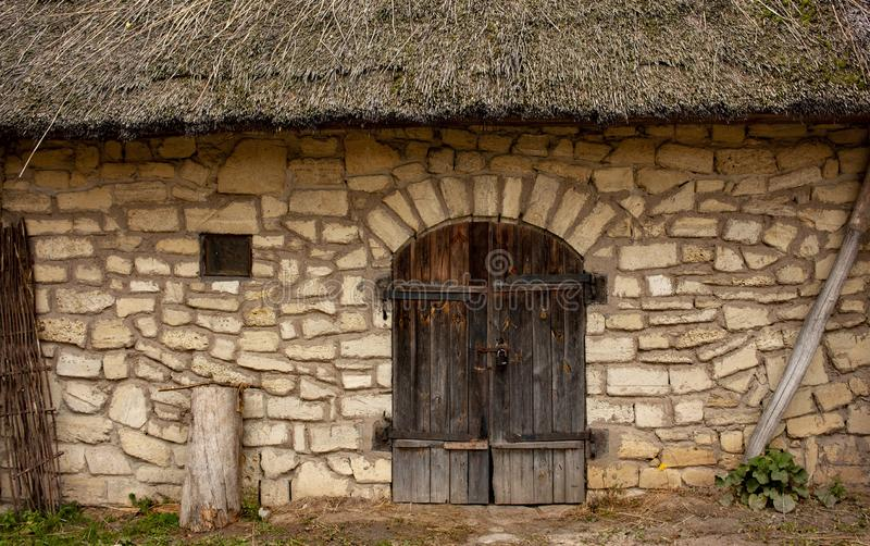 Facade of an old stone brick wall with wooden doors, a small window and thatched roof royalty free stock images