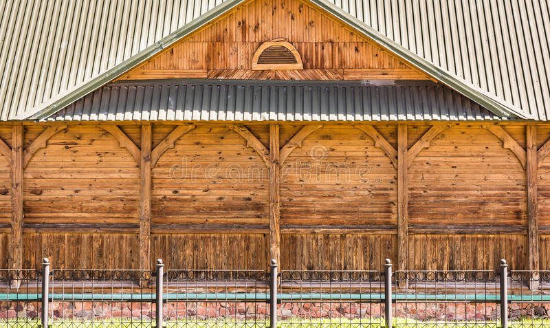 The facade of part of an old wooden building with decorative columns and a roof made of metal profile, windowless wall stock image