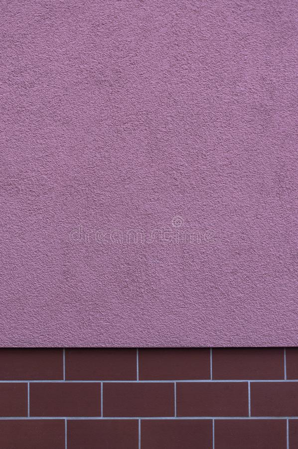 Facade plastered in striking color pink, the base is tiled as a protection against pollution with small, narrow and elongated. Tiles in burgundy, the design is royalty free stock photography