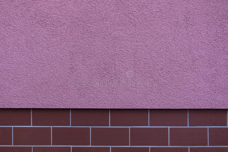 Facade plastered in striking color pink, the base is tiled as a protection against pollution with small, narrow and elongated. Tiles in burgundy, the design is stock photo