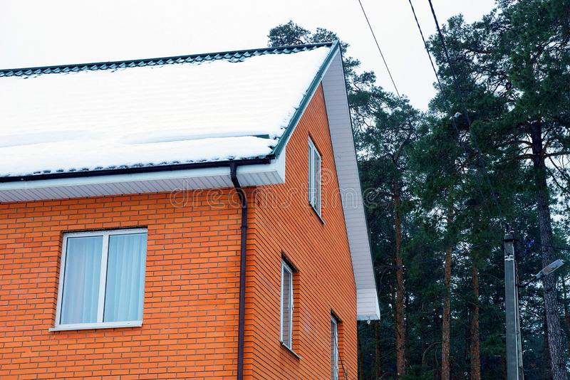 Part of a brick red house with windows with white snow on the roof against the background of green pine and sky stock photo