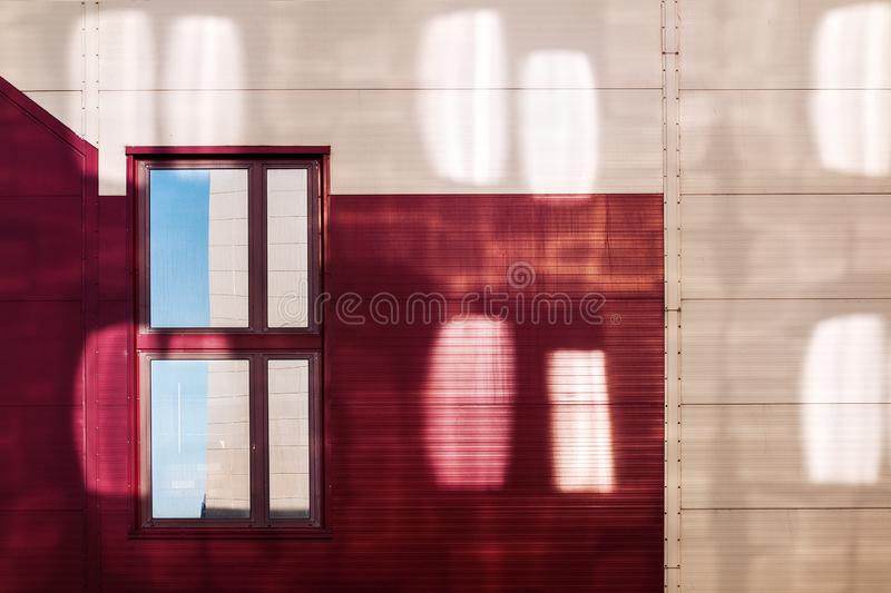 Facade of a red-yellow building with reflections from the windows of the neighboring building. the single window reflects the corn. Er of the building opposite stock photography
