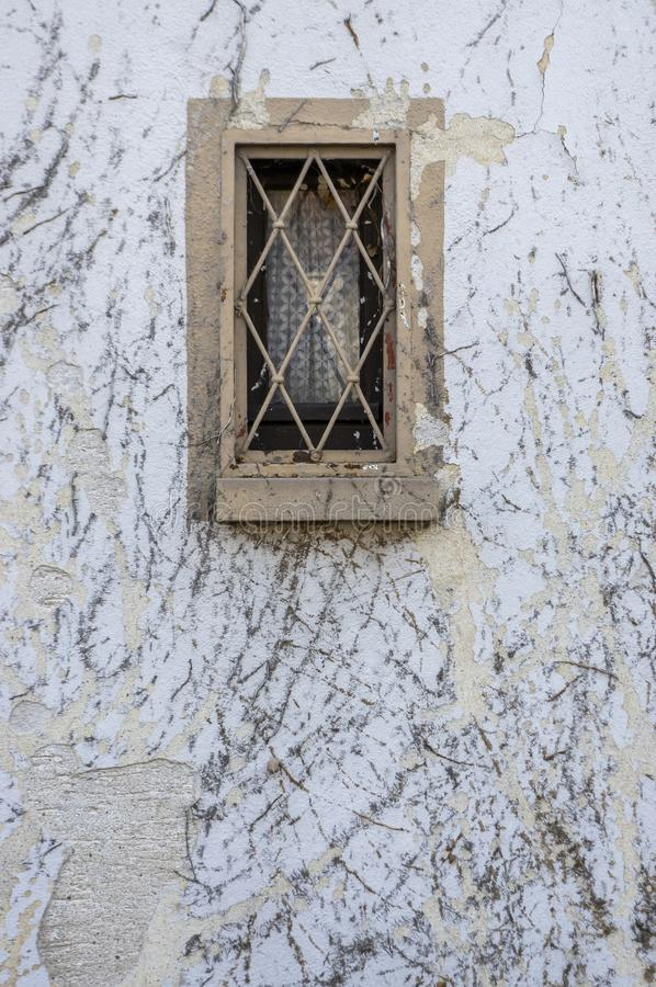 Facade with remains of common ivy vegetation are damaged by the plaster and the paint and small wooden windows with window bars as royalty free stock photo