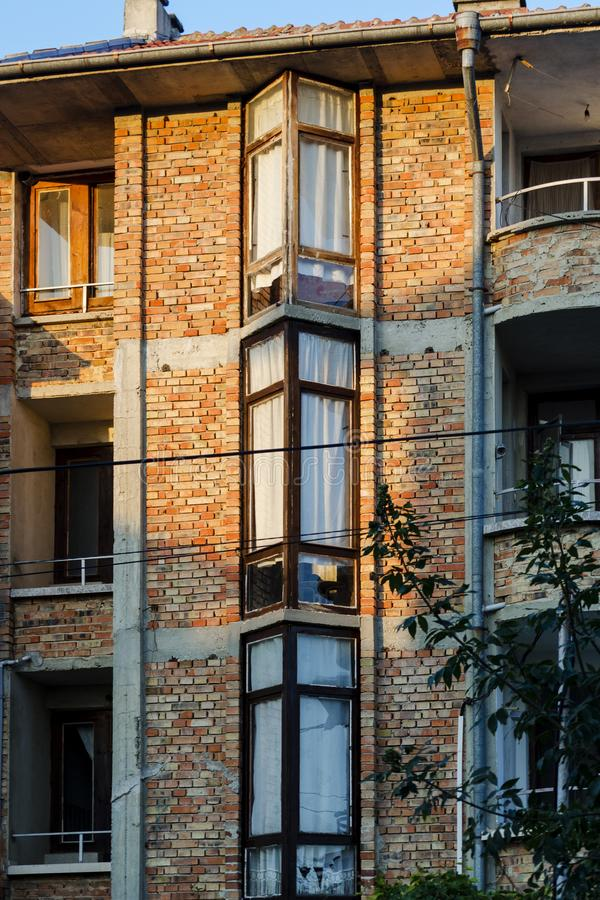 The facade of a residential unfinished building of faded red brick. Three-storey home typical of Europe at sunset. House with. Balconies and windows with white royalty free stock image