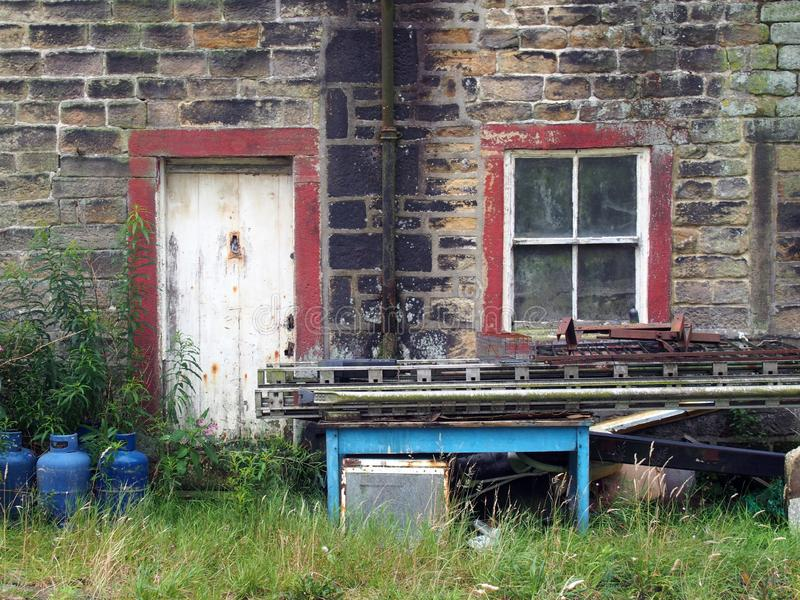 A shabby abandoned rural house with dirty windows and peeling paint overgrown with weeds with scrap and junk piled stock image