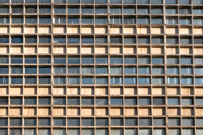 Facade of skyscraper. Many windows of geometric. Wall with lots of identical window rows stock photo