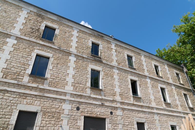 Facade of a stone building with windows. A facade of a stone building with windows stock images