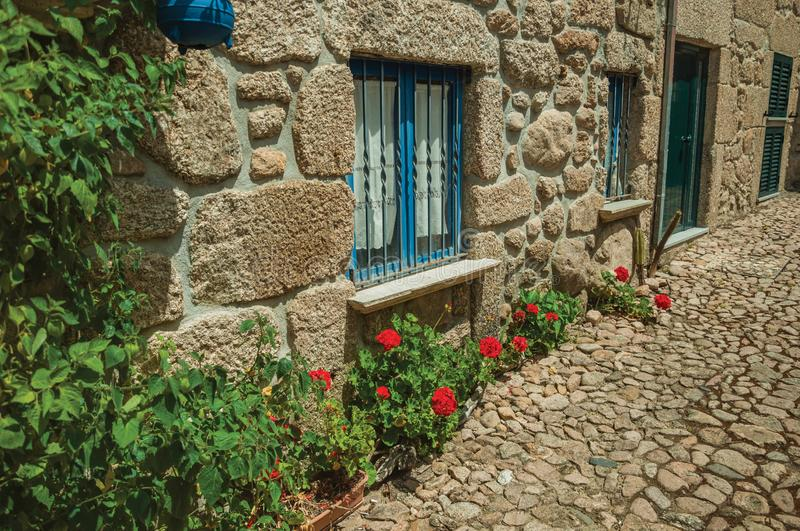 Facade of stone house with barred windows and flowers stock photo