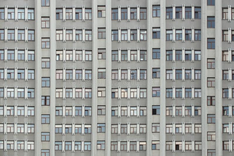 The facade of a tall office building with numerous windows. Architecture of the mid-twentieth century. A monumental. Building made of reinforced concrete. Wall stock photography