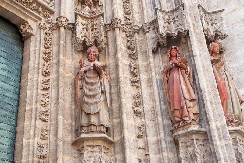 Facade with 16th century sculptures of Roman Catholic Seville Cathedral , Spain. Priest and women reading Bible royalty free stock image
