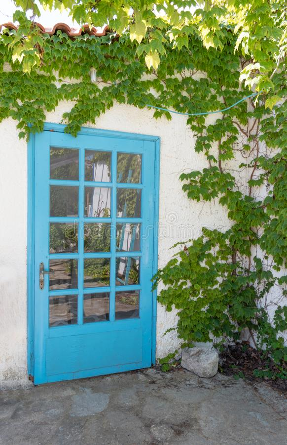 Facade of traditional white greek house with blue door and window and reflected on glass stock images