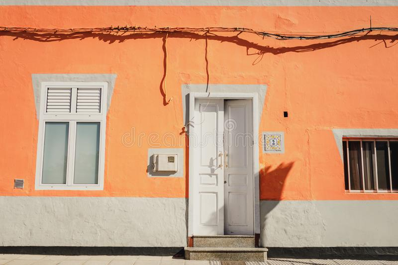 A facade of a vibrant orange house with a window and an open white front door in Galdar, Gran Canaria. A facade of a vibrant peachy orange house with a window stock photo