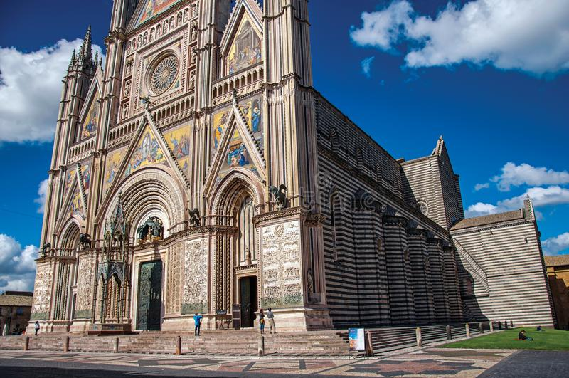 Facade view of the opulent and monumental Orvieto Cathedral Duomo with people in Orvieto. Orvieto, Italy - May 17, 2013. Facade view of the opulent and stock photos