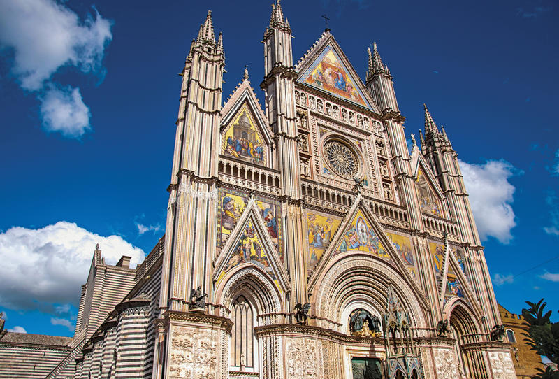 Facade view of the opulent and monumental Orvieto Cathedral in Orvieto. Facade details of the opulent and monumental Orvieto Cathedral Duomo under sunny blue stock images