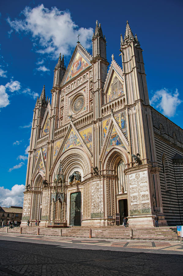 Facade view of the opulent and monumental Orvieto Cathedral in Orvieto. Facade view of the opulent and monumental Orvieto Cathedral Duomo under sunny blue sky royalty free stock image