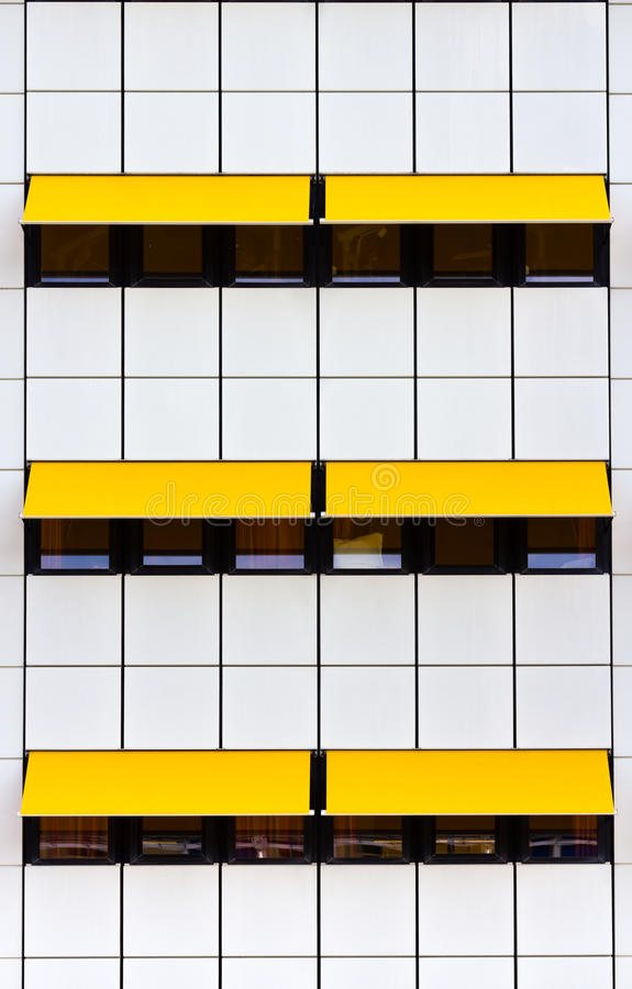 Facade with white tiles and yellow awnings. Crop of modern facade with white tiles and yellow awnings stock image