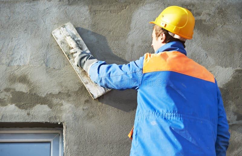 Facadebyggmästareplasterer på arbete royaltyfri bild