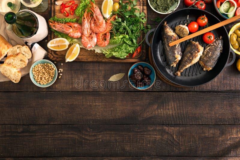 Faccia festa la tavola con gamberetto, il pesce grigliato, l'insalata, gli spuntini, vino bianco immagini stock