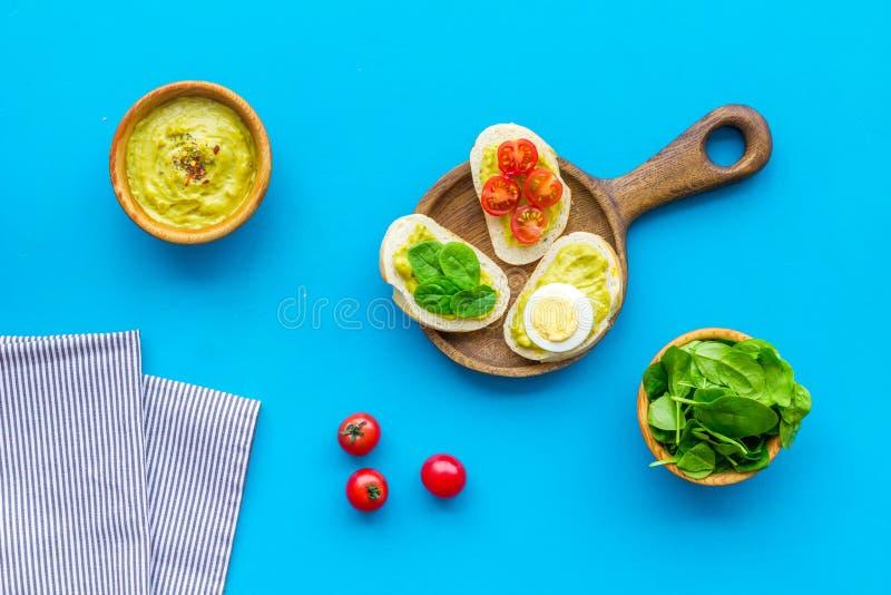 Faccia le Bruschette dell'avocado Pani tostati con le verdure ed il guacamole sulla vista superiore del fondo blu fotografia stock