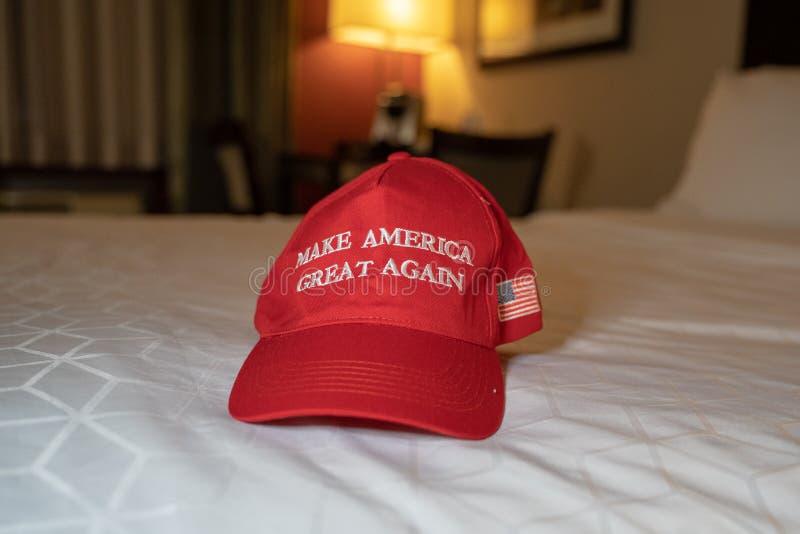 Faccia le grande dell'America il cappello rosso si siede ancora che su un letto Concetto per presidente Donald Trump ri- fotografia stock