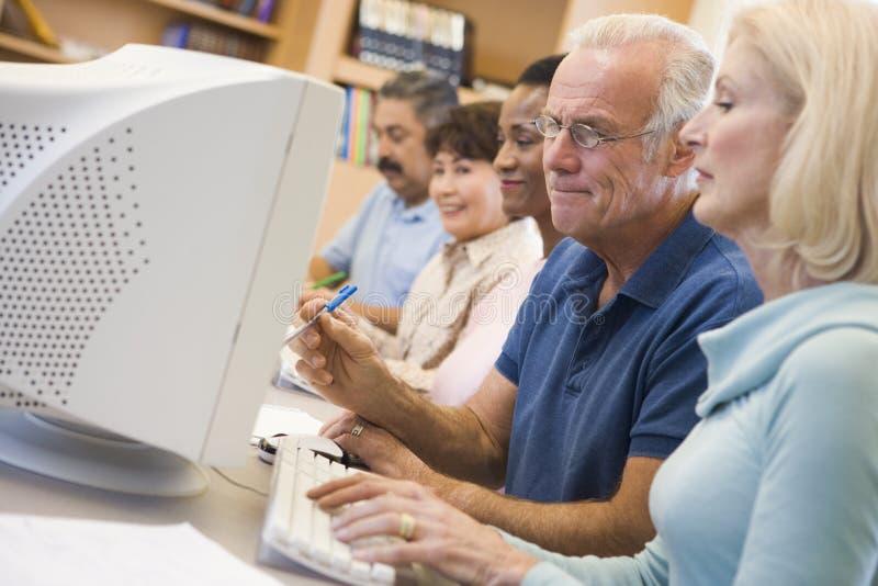 Faccia maturare gli allievi che imparano le abilità del calcolatore immagine stock