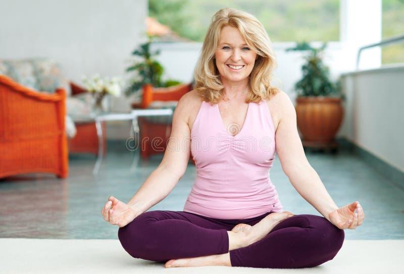Faccia maturare la donna nella posizione di yoga immagini stock libere da diritti
