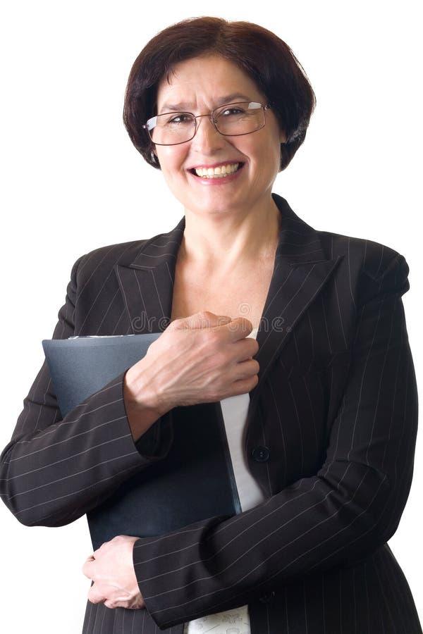 Faccia maturare la segretaria o la donna di affari sorridente attraente isolata immagini stock