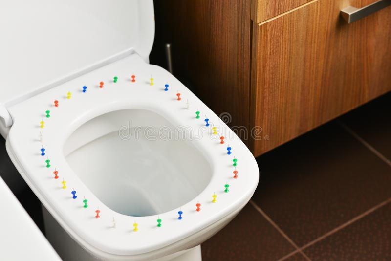 Faccia soffrire ed altri sintomi degli emorroidi esterni, immagine astratta con la ciotola di toilette e puntine da disegno vario fotografia stock