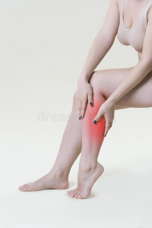 Faccia soffrire in gambe del ` s della donna, massaggio dei piedi femminili su fondo beige immagini stock libere da diritti