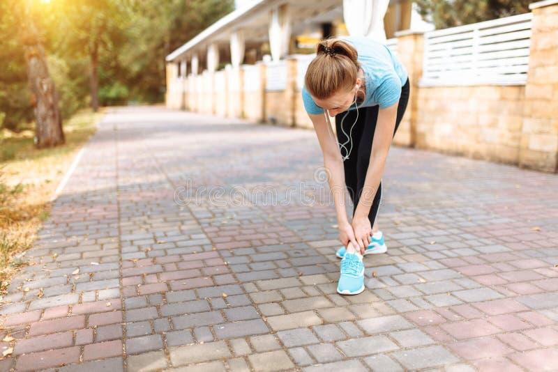 Faccia soffrire nella gamba della ragazza dopo gli sport il funzionamento, l'addestramento di mattina, allungamento della gamba immagini stock libere da diritti
