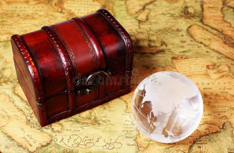 Faccia tesoro la scatola ed il globo sul fondo antico della mappa fotografia stock libera da diritti