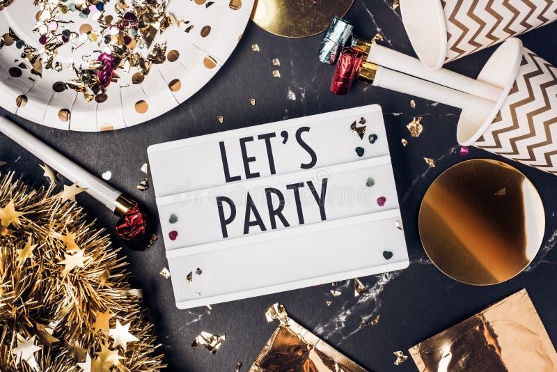 Facciamo festa sulla scatola leggera con la tazza del partito, il ventilatore del partito, il lamé, conf immagine stock libera da diritti