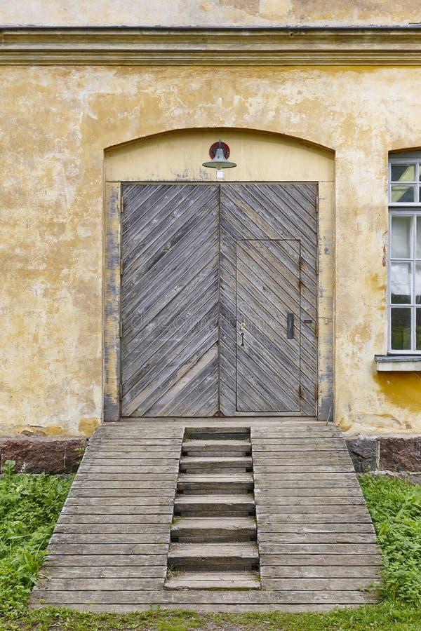Facciata antica della fabbrica con le porte e la rampa di legno immagini stock libere da diritti