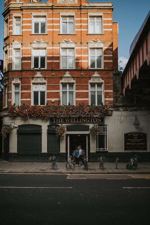 Facciata classica della costruzione di appartamenti nel centro urbano di Londra, osservato dal marciapiede e dalla gente opposti  immagini stock