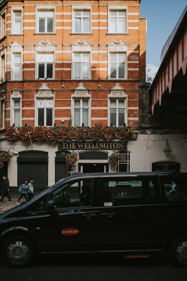 Facciata classica della costruzione di appartamenti nel centro urbano di Londra, osservato dal marciapiede opposto mentre un incr immagine stock libera da diritti
