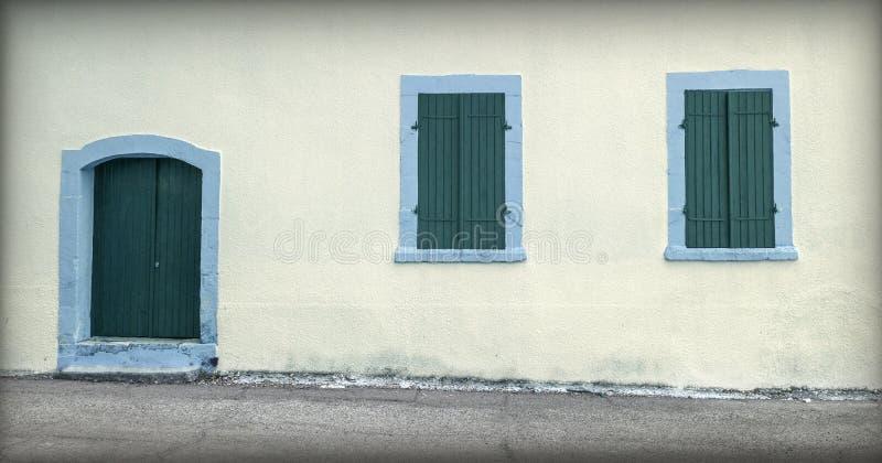 Facciata con la vecchia porta e piccole finestre immagini stock