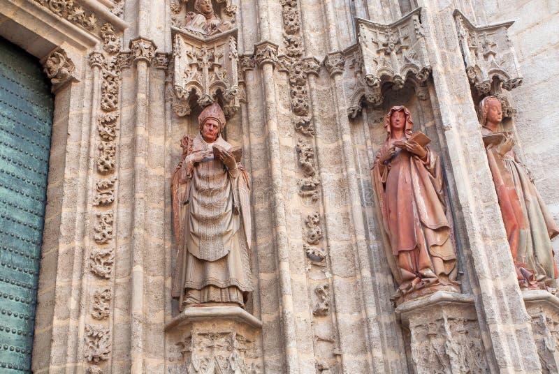 Facciata con le sculture del XVI secolo di Roman Catholic Seville Cathedral, Spagna Sacerdote e bibbia della lettura delle donne immagine stock libera da diritti