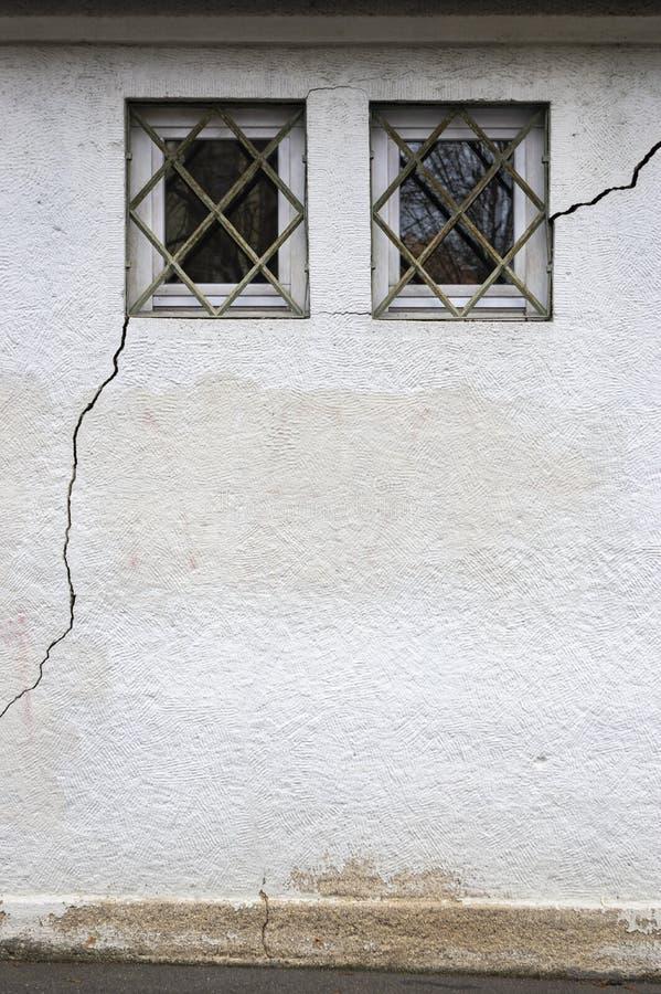 Facciata con 2 piccoli, le finestre escluse attraverso cui una crepa lunga ed ampia di circa 3 metri nella muratura funziona fotografia stock libera da diritti